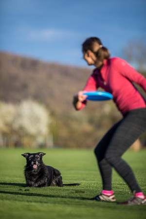 Young woman throwing freisbee to her black dog outdoors (shallow DOF, sharp focus Banco de Imagens - 106267090