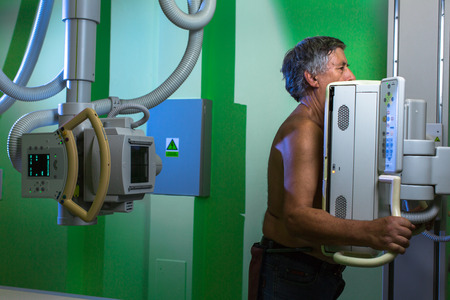 Healthcare Concept - Senior male patient undergoing an X-ray examination in a modern hospital