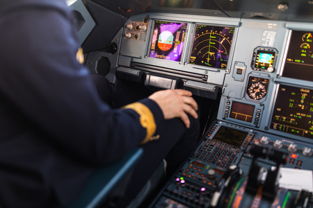 Pilots hand accelerating on the throttle in  a commercial airliner airplane flight cockpit during takeoff Фото со стока