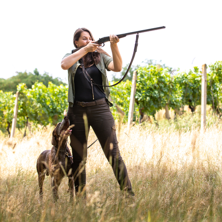 Autumn hunting season. Hunting. Outdoor sports. Woman hunter in the woods with her well trained dog Foto de archivo