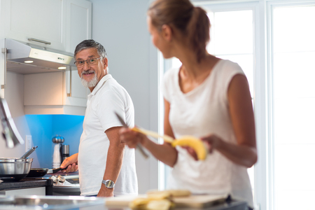 Senior man cooking in a bright modern kitchen together with his daughter, having a blast (color toned image) 写真素材