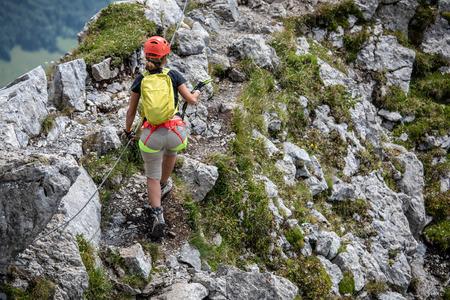 Pretty, female climber on a via ferrata - climbing on a rock in Swiss Alps 版權商用圖片