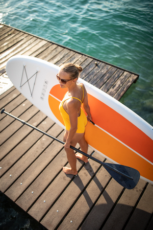 SUP Stand up paddle board concept - Pretty, young woman paddle boarding on a lovely lake in warm late afternoon light Stock Photo