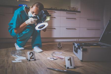 Especialista forense en traje de protección tomando fotos en la escena de un crimen