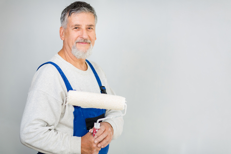 Senior man posing with a paint roller after having paint a white wall