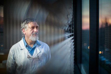 Senior chemistry professor by a classroom window, looking pensive (shallow DOF; color toned image)
