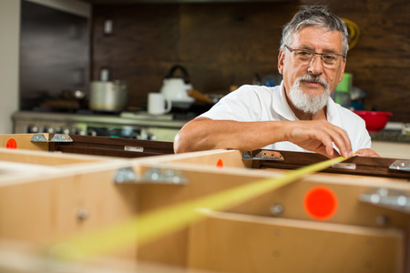DIY concept - Senior man doing putting together kitchen cabinets