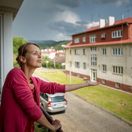 Pretty, young woman checking wether it is raining already from the balcony of her appartment Stock fotó
