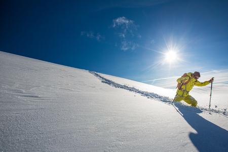 High altitude mountain explorer walking through deep snow in high mountains on a freezing winter day Stock Photo