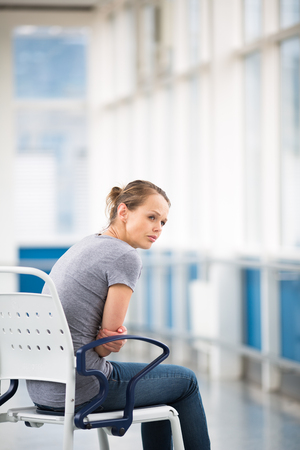Female patient, sitting in a wheelchair for patients feeling not well enough to stand, waiting to be taken care of in a modern hospital (shallow DOF; color toned image)