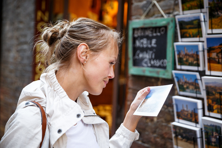 Young woman messagingusing app on her smart-phone in a city street context (shallow DOF; color toned image)