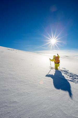 High altitude mountain explorer walking through deep snow in high mountains on a freezing winter day 스톡 콘텐츠