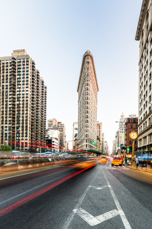 NEW YORK CITY USA - August 24th 2014: Motion blurred traffic in front of the Flatiron building at Fifth Avenue in Manhattan. Flatiron is an iconic buiding of NYC.