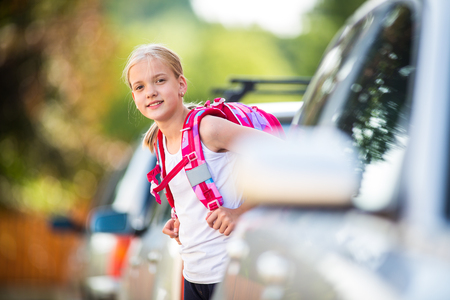 Cute little girl going home from school, looking well before crossing the street
