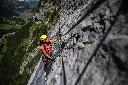 Pretty, female climber on a via ferrata - climbing on a rock in Swiss Alps Stock Photo