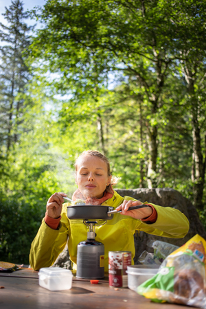 Female hikerclimber preparing supper on gas burner in a camp Banco de Imagens