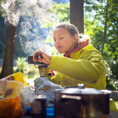 Female hikerclimber preparing supper on gas burner in a camp 写真素材