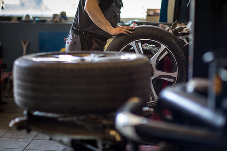 Wheel balancing or repair and change car tire at auto service garage or workshop by mechanic Archivio Fotografico