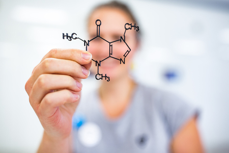 Young woman holding up a molecular model of nicotin Stock Photo