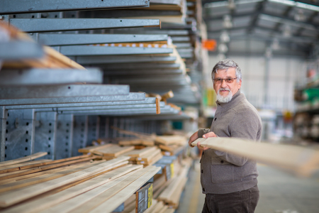 DIY concept -Senior man choosing and buying construction wood in a DIY store for his DIY home re-modeling project Stock Photo