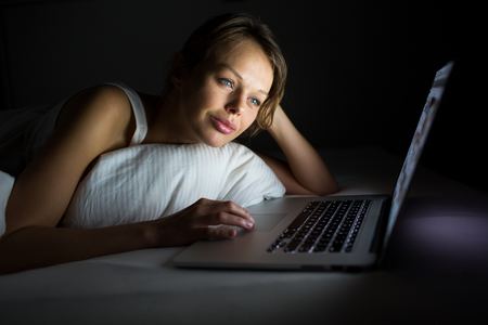 Pretty, young woman using her laptop computer in bed (color toned image; shallow DOF)