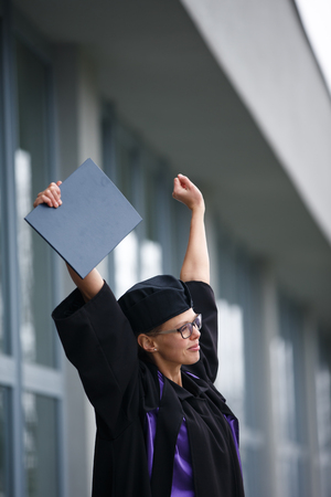 Pretty, young woman celebrating joyfully her graduation - cheking her diploma, happy/impressed with the title she received (color toned image; shallow DOF)