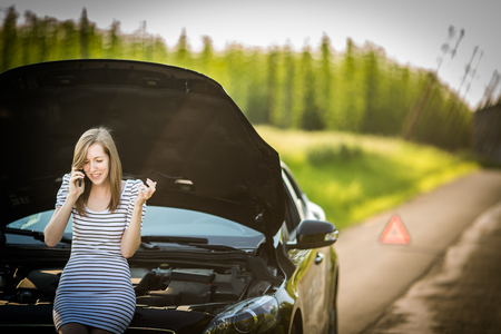 Pretty, young woman calling the roadside service/assistance after her car has broken down Stock Photo