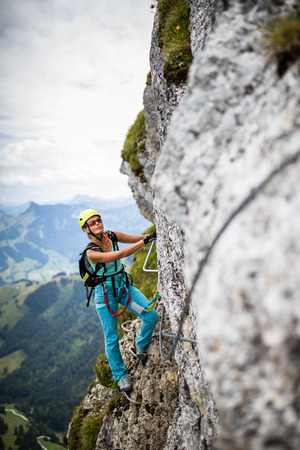 Pretty, female climber on a via ferrata -  climbing on a rock in Swiss Alps