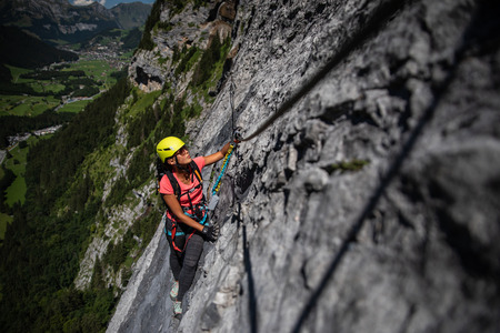 Pretty, female climber on a via ferrata - climbing on a rock in Swiss Alps Stok Fotoğraf