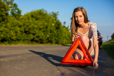Pretty, young woman setting the safety triangle on the roadside after her car has broken down Stock Photo