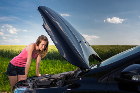 Pretty, young woman by the roadside after her car has broken down Stock Photo