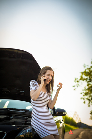 Pretty, young woman calling the roadside serviceassistance after her car has broken down Stock Photo