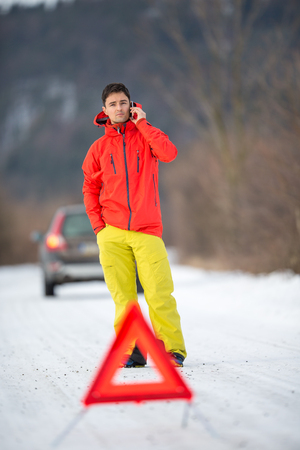 Young man calling car assistance service after his car has broken down on a cold winter day