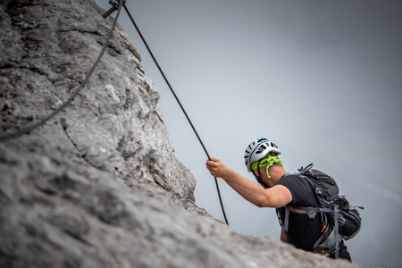 Pretty, female climber on a via ferrata - climbing on a rock in Swiss Alps Archivio Fotografico