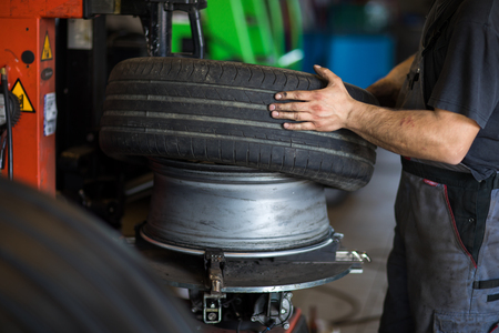 Tyre change - wheel balancing or repair and change car tire at auto service garage or workshop by mechanic Banque d'images - 108984380