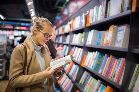 Pretty, young female choosing a good book to buy in a bookstore Фото со стока