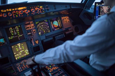 Mano del pilota che accelera sull'acceleratore in una cabina di pilotaggio di volo di un aereo di linea commerciale durante il decollo Archivio Fotografico