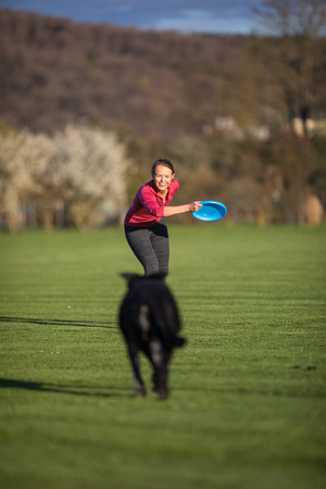 Portrait of a black dog running fast outdoors towards a woman