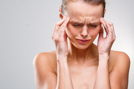 Beautiful woman suffering from acute headache over grey clean background