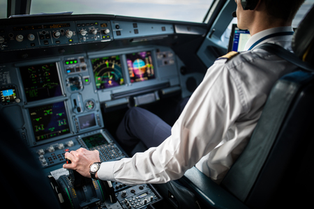 Pilots hand accelerating on the throttle in  a commercial airliner airplane flight cockpit during takeoff Banco de Imagens