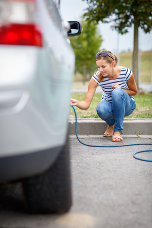 Young woman checking the car tyre pressure - inflating it