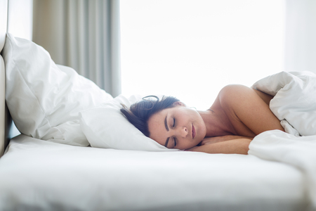 Beautiful young woman sleeping on bed at bedroom Stock Photo