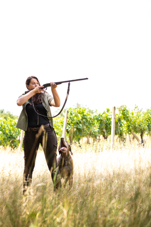 Autumn hunting season. Hunting. Outdoor sports. Woman hunter in the woods with her well trained dog Stock Photo