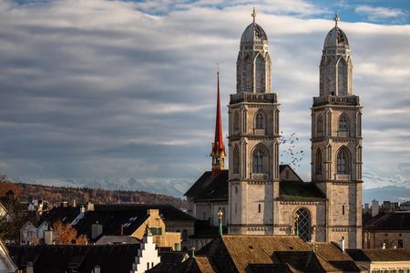 Zurich, Switzerland - view of the Grossmunster church with beautiful mountains in the background Stock Photo