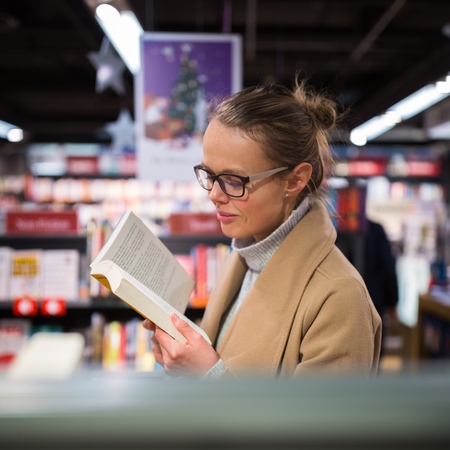Pretty, young female choosing a good book to buy in a bookstore Stock Photo