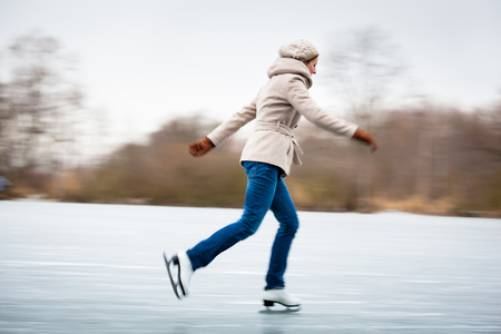 Young woman ice skating outdoors on a pond on a freezing winter day 写真素材