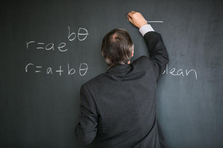 Senior male teacher teaching mathematics, writing on the blackboard