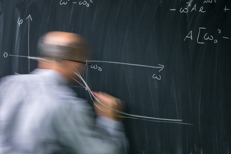 Math teacher drawing   fuction graph on a blackboard during mathclass (motion blurred image) Stock Photo