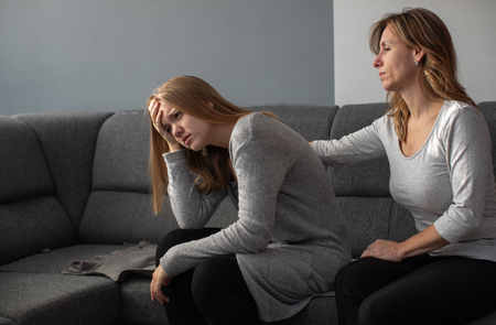 Depressed teen suffering from anxiety being taken care of by her caring mother Stock Photo