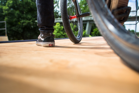 Young man with his BMX bike on a ramp, about to do some insane tricks. BMX concept. Stock Photo